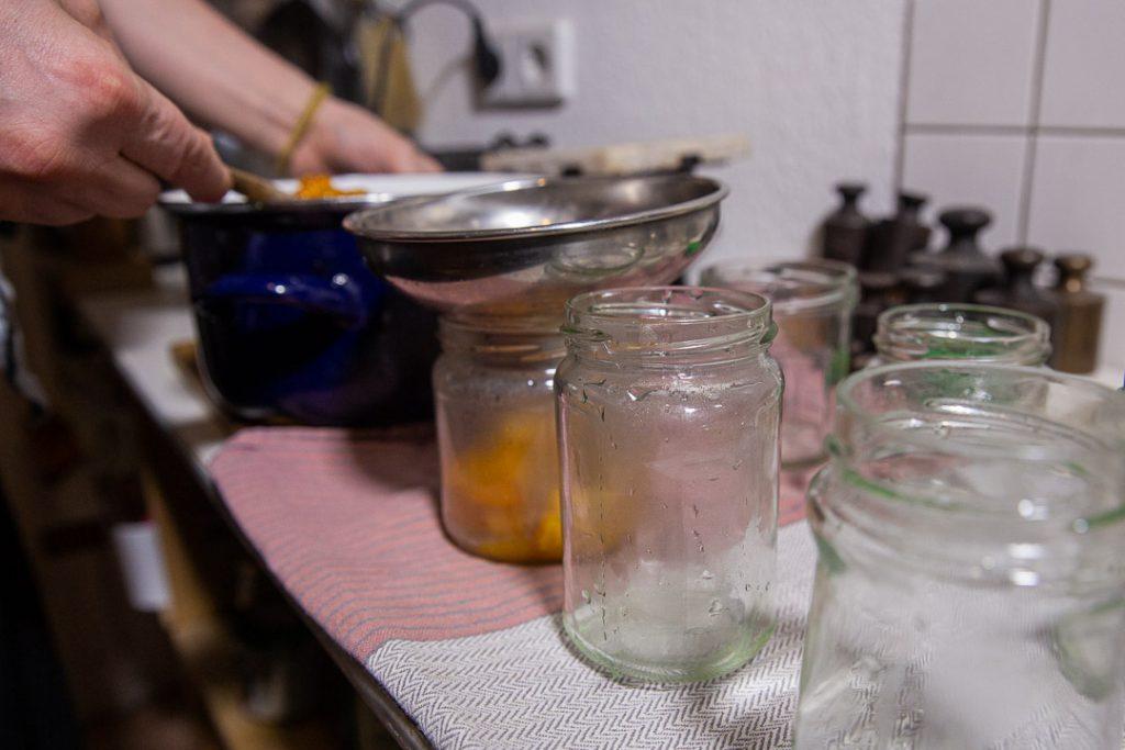 Orangenmarmelade in die Gläser füllen